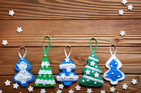 Handmade rustic green felt Christmas tree decorations flat lying on wooden table