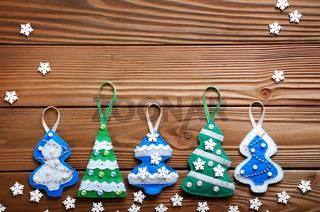 Handmade rustic green felt Christmas tree decorations flat lying on wooden table