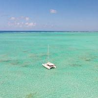 Aerial view of Catamaran boat sailing in turquoise lagoon of Ile aux Cerfs Island lagoon in Mauritius.