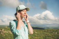 Fitness runner woman closing his eyes listening to music on the nature. Portrait of beautiful girl wearing earphones earbuds and running cap. against the background of a green field and blue sky