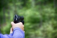 Woman shoots from air gun in forest