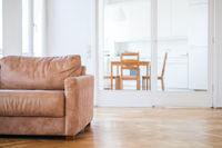 empty couch seat in  living room with wooden floor,  and kitchen in background