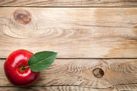Red Apple with Green Leaf on Wooden Table