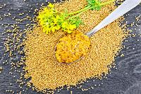 Sauce mustard Dijon in spoon with flower on board top