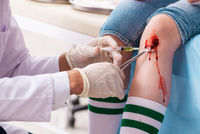 Leg injured young woman visiting male doctor