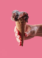 The hand of a man holds a waffle cone with fruit, ice cream decorated with coconut chips on a pink background with copy space.
