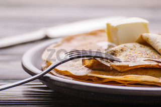 Stack of French crepes with butter in ceramic dish on wooden kitchen table