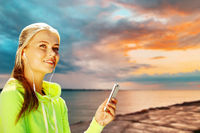 woman listening to music on smartphone at seaside