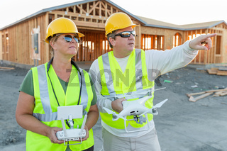 Workers with Drone Quadcopter Inspecting Photographs on Controller At Contruction Site