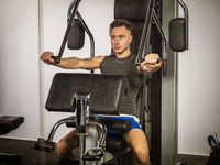Muscular young man, training pecs on gym machine