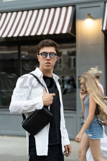 Young guy in round sunglasses posing on camera.