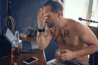 Freelance guy with a naked torso smokes and works on a laptop