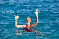 The young woman in a red bathing suit on sea background greeting waving