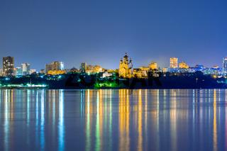 Night View of the city of Khabarovsk from the Amur river. Blue night sky. The night city is brightly lit with lanterns.