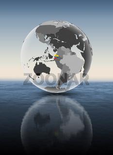 Ecuador on translucent globe above water