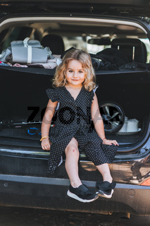 A small, beautiful girl is sitting in car