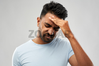 unhappy indian man suffering from headache