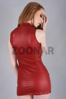 Vollbusige Rothaarige gekleidet in einem sexy roten Kleid mit einem Reissverschluss