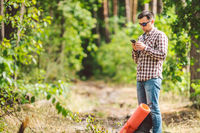 Hipster young man with backpack using smart phone on beautiful nature.Travel concept. Outdoor travel. Travel and explore. Backpacker male Going in forest Gps Route. Portrait hiker using mobile phone