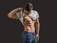 Young muscleman undressing on dark background