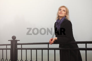 Young fashion woman in black coat leaning on handrail in a fog outdoor