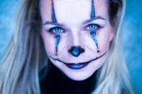 Halloween clown woman portrait posing over concrete wall