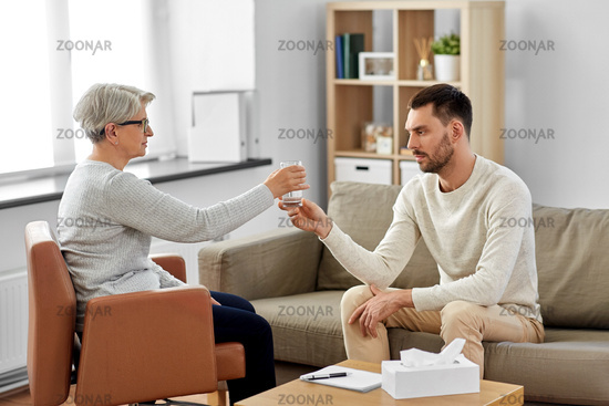 senior psychologist giving water to man patient