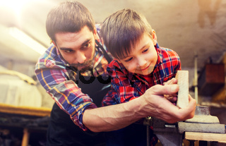 father and little son with wood plank at workshop