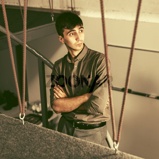 Young handsome business man standing on the steps in office