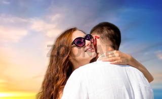happy couple hugging over sunset sky background