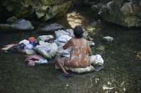 Filipino elderly woman washing clothes in the river. Philippines. Island Katiklan