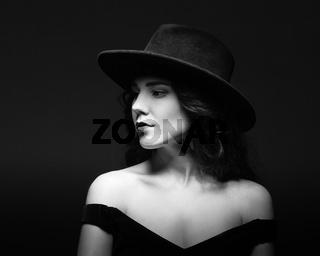 Profile portrait of a beautiful lady wearing a black hat