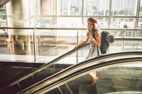 Portrait Smiling Woman Wearing Hat In Airport At Escalator. people traveling with hand luggage. Theme tourism and transport. Caucasian girl with coffee in airport terminal on an escalator