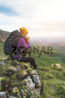 Smiling girl traveler in a yellow hat and a pair of sunglasses ssitting at the foot of epic rocks with a backpack next and looks away