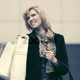 Happy young fashion woman with shopping bags in city street