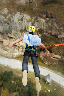 A man in a helmet jumps ropeup with an empty flag in the mountains. Extreme sports. Leisure. Top view