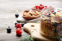 Fruit healthy muesli in glass jar on kitchen wooden table