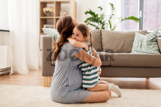 pregnant mother and daughter hugging at home
