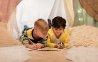 boys with magnifier and map in kids tent at home