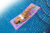 Woman on air mattress in swimming pool