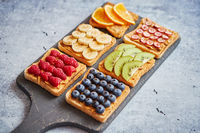Wholegrain bread slices with peanut butter and various fruits