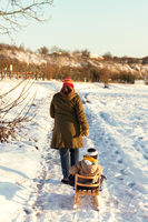 Little toddler walking outdoors in a snowy winter scene with his mom.