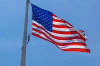 American flag on a pole. The flag flies by the wind