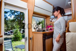 Woman cooking in camper, motorhome RV interior