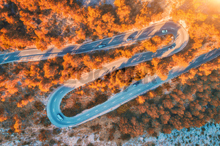 Aerial view of mountain curve road with cars, autumn forest