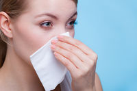 Sick woman using paper tissue, headcold problem