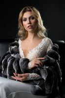 Slim blonde in lace dress and fur-coat on the sofa