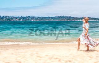 Woman in flowing dress on beach in Sydney Australia