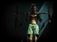 Young man hanging from gym equipment in dark
