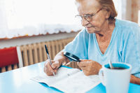 Senior woman in her 80s enjoys solving a crossword puzzle